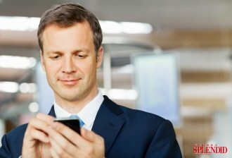 Businessman Text Messaging At Airport