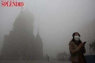 A woman wearing a mask checks her mobile phone during a smoggy day in Harbin