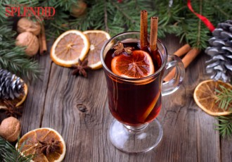 Mulled wine, sliced dried orange, cinnamon sticks, anise stars and candle with pine brunch